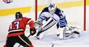 Johnny Gaudreau of the Calgary Flames and Michael Hutchinson of the Winnipeg Jets