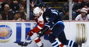 Jacob Trouba of the Winnipeg Jets and Riley Sheahan of the Detroit Red Wings