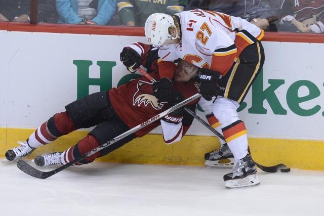 Calgary Flames Dougie Hamilton taking down Arizona Coyotes forward Max Domi