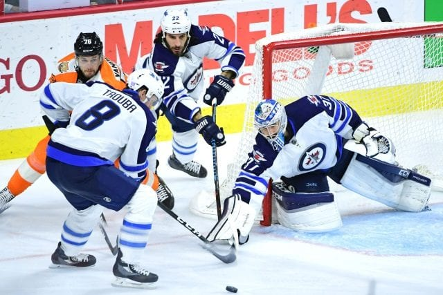 Connor Hellebuyck and Jacob Trouba of the Winnipeg Jets