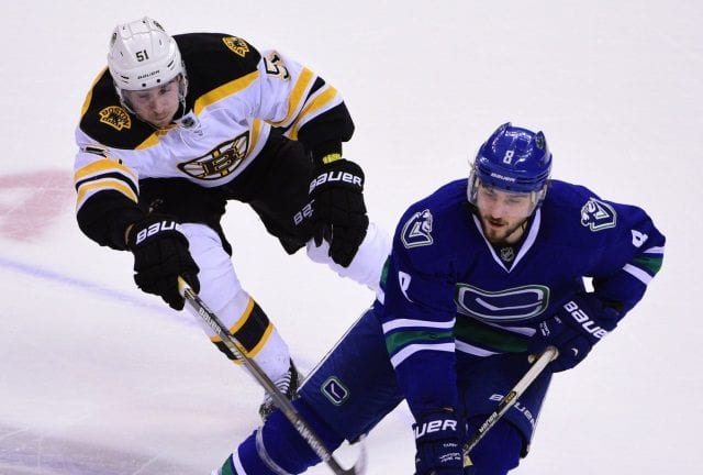 Ryan Spooner of the Boston Bruins and Chris Tanev of the Vancouver Canucks