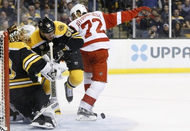 David Pastrnak of the Boston Bruins and Andreas Athanasiou of the Detroit Red Wings